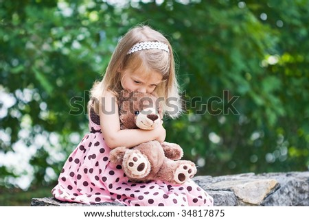 Adorable little girl giving her teddy bear a kiss on the head. Shallow DOF.