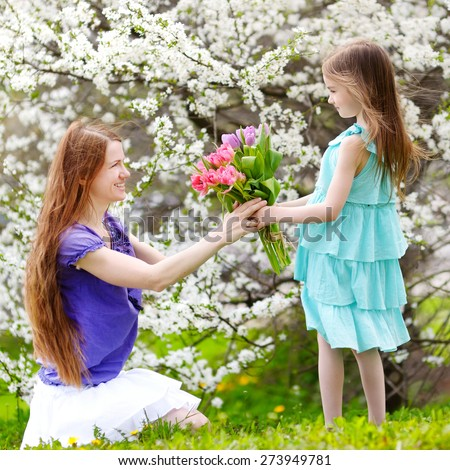 Adorable little girl handing tulips to her mother in blooming cherry garden on beautiful spring day - stock photo