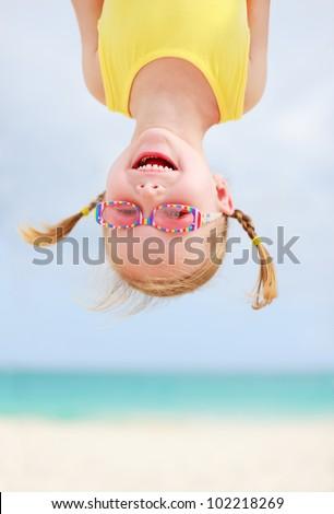 Adorable little girl hanging upside down having fun - stock photo