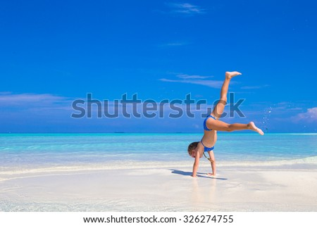 Adorable little girl have fun at beach during summer vacation - stock photo