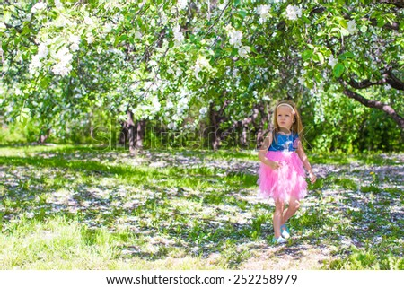 Adorable little girl have fun in blossoming apple tree garden at may - stock photo