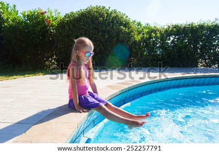 Adorable little girl have fun outdoors near swimming pool - stock photo