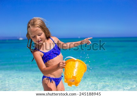 Adorable little girl have fun with beach toy during tropical vacation