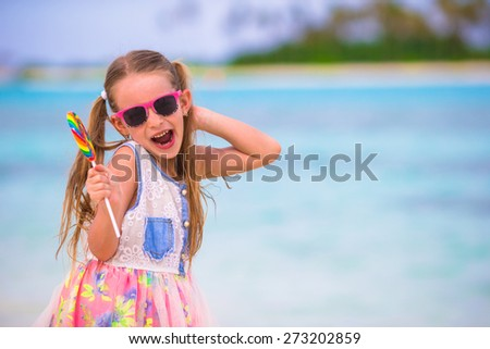 Adorable little girl have fun with lollipop on the beach - stock photo