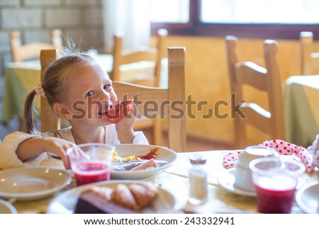 Adorable little girl having breakfast at restaurant - stock photo