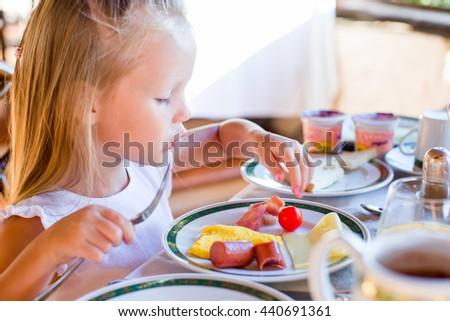 Adorable little girl having breakfast at restaurant - stock photo