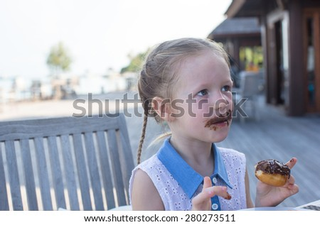 Adorable little girl having breakfast eating chocolate donut at outdoor cafe - stock photo