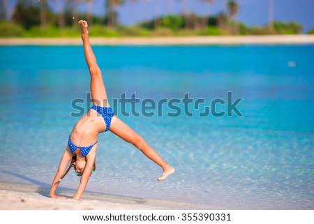 Adorable little girl having fun making cartwheel on tropical white sandy beach