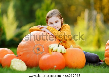 Adorable little girl having fun on a pumpkin patch on beautiful autumn day outdoors