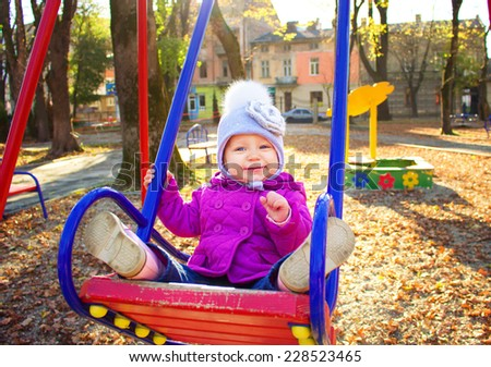 Adorable little girl having fun on a swing outdoor - stock photo