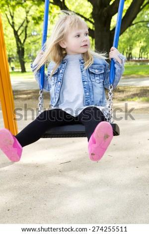 Adorable little girl having fun on a swing outdoor - stock photo