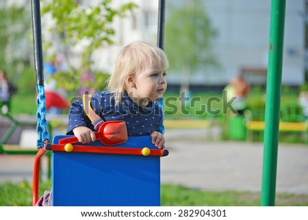 Adorable little girl having fun on a swing outdoor