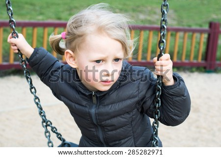 Adorable little girl having fun on a swing outdoor on the playgr - stock photo