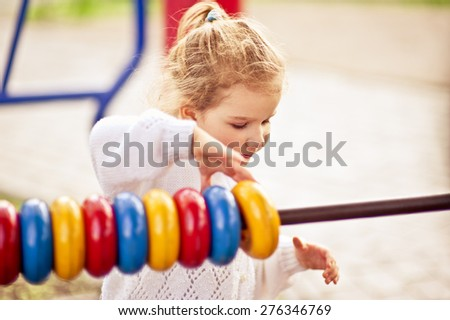 Adorable little girl having fun on the playground playing outdoors closeup - stock photo