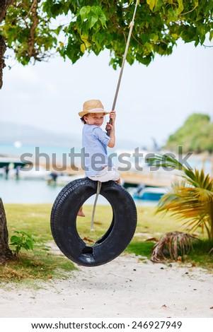 Adorable little girl having fun on tire swing on summer day - stock photo