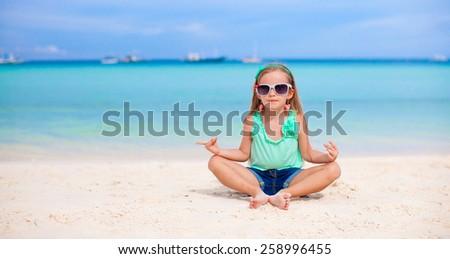 Adorable little girl having fun on white beach - stock photo