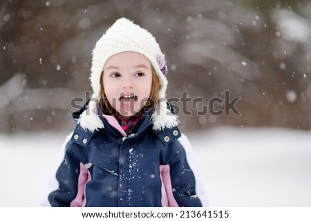 Adorable little girl having fun on winter day - stock photo