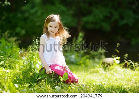 Adorable little girl having fun outdoors on beautiful summer day - stock photo