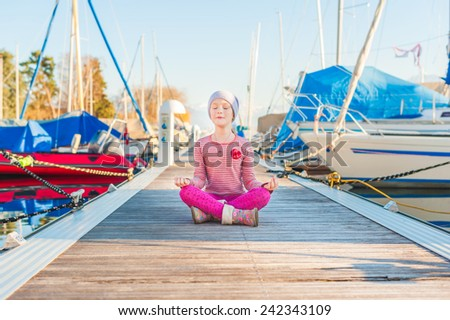 Adorable little girl having fun outdoors, resting on a pier on a nice sunny spring day - stock photo