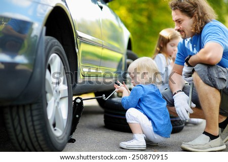 Adorable little girl helping her father to change a car wheel outdoors on beautiful summer day - stock photo