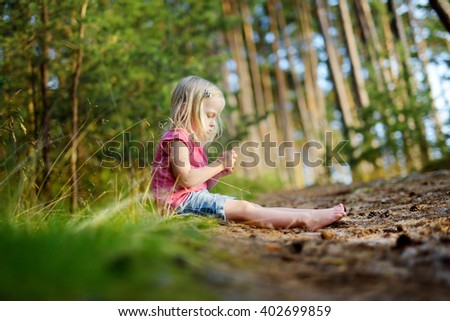 Adorable little girl hiking in the forest on hot summer day