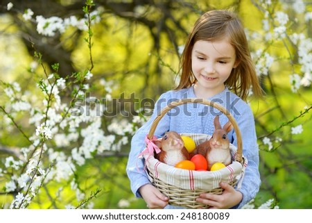 Adorable little girl holding a basket of Easter eggs in blooming spring garden on Easter day - stock photo
