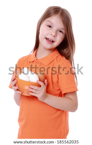 Adorable little girl holding a bowl of eggs isolated over white - stock photo