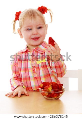 Adorable little girl holding a strawberry sitting at the table-Isolated on white background