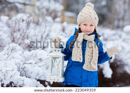 Adorable little girl holding Christmas lantern outdoors on beautiful winter snow day - stock photo