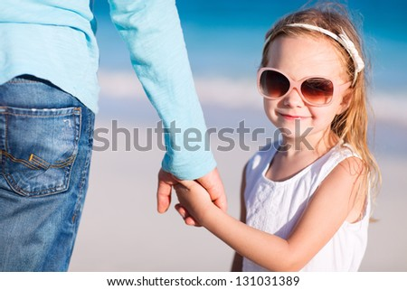 Adorable little girl holding her father hand