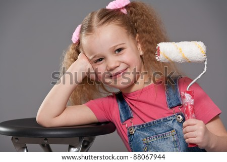 Adorable little girl holding paint roller - stock photo