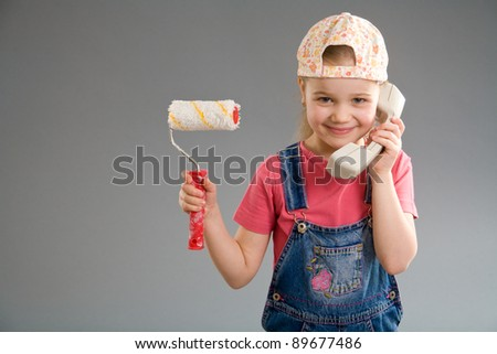 Adorable little girl holding paint roller and phone receiver - stock photo