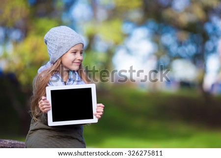 Adorable little girl holding tablet PC outdoors in autumn sunny day - stock photo