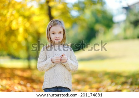 Adorable little girl holding yellow maple leaf on beautiful autumn day