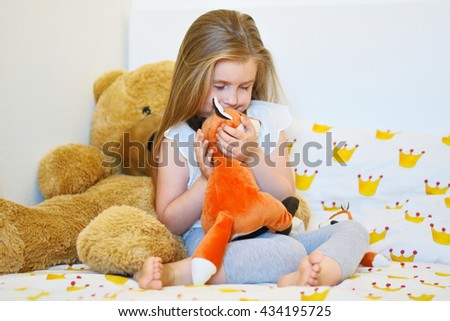 Adorable little girl hugging fox plush toy in bed - stock photo