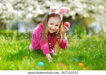 Adorable little girl hunting for easter egg in blooming spring garden on Easter day - stock photo