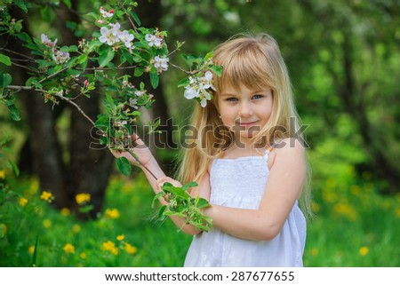 Adorable little girl i blooming apple tree garden on spring day