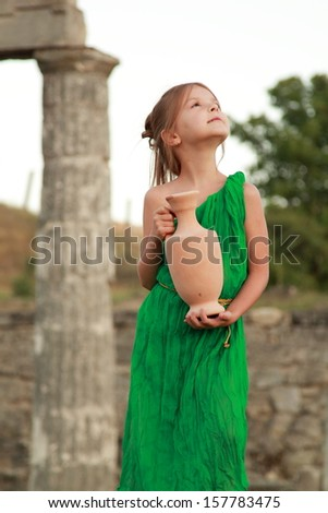 Adorable little girl in a beautiful dress with a vintage antique amphora / Excavations on Mount Mithridates city of Kerch, Ukraine - the ruins of the ancient city of Pantikapaion - stock photo