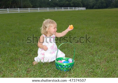 Adorable little girl in a field with her Easter basket full of eggs - stock photo