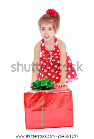 Adorable little girl in a red dress with white polka dots with a large gift box, isolated on white background - stock photo