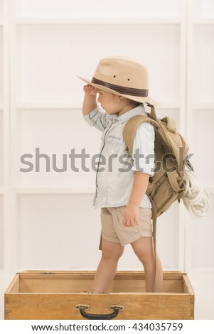 Adorable little girl in a safari hat and explorer clothes playing safari in a wooden suitcase, indoor shot. Children's play concept - stock photo