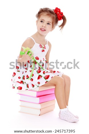 Adorable little girl in a summer dress sitting on a pile of books.Isolated on white background - stock photo