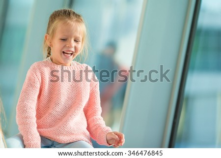 Adorable little girl in airport have fun waiting for boarding - stock photo