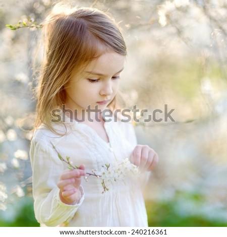 Adorable little girl in blooming cherry garden - stock photo