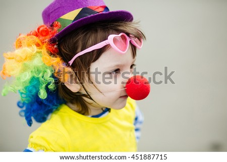 Adorable little girl in clown costume outdoors at summer day - stock photo
