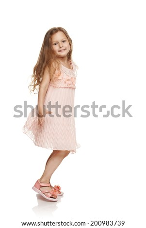 Adorable little girl in cream colored dress running into frame in full length over white background - stock photo