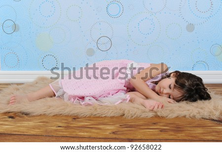 adorable little girl in dress asleep on furry brown rug - stock photo