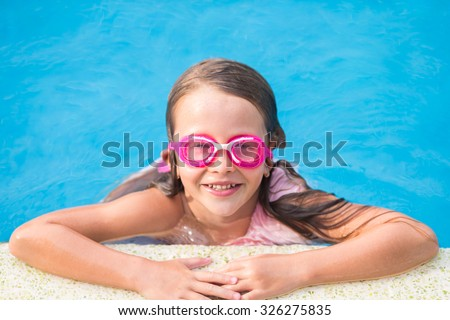 Adorable little girl in outdoor swimming pool - stock photo