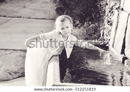 Adorable  little girl in princess dress near the fountain outdoor