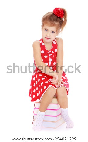 Adorable little girl in red dress sitting on a pile of books. Isolated on white.